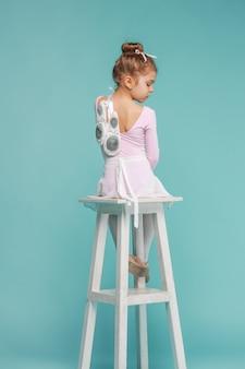 Die kleine balerina-tänzerin auf blauem hintergrund
