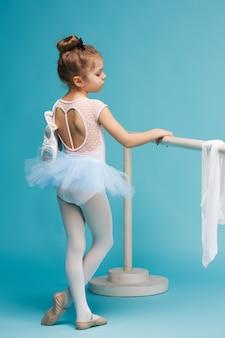 Die kleine balerina-tänzerin auf blauem raum