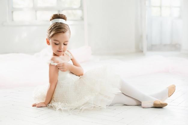 Die kleine ballenpresse in weißem tutu im unterricht beim ballett