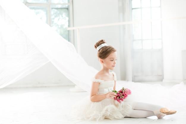 Die kleine ballenpresse in weißem tutu im unterricht in der ballettschule