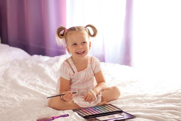 Die kleine süße blondine lächelt drei bis vier jahre lang mit einem haarschnitt neben einem spiegel mit kosmetika und pinseln