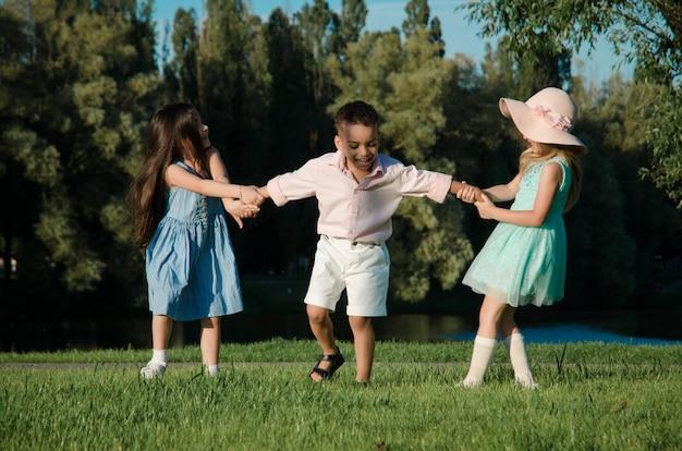 Die kleinen kinder spielen auf dem rasen. zwei mädchen und ein junge