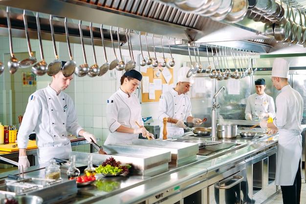 Die köche bereiten ihre mahlzeiten in der küche des restaurants zu.