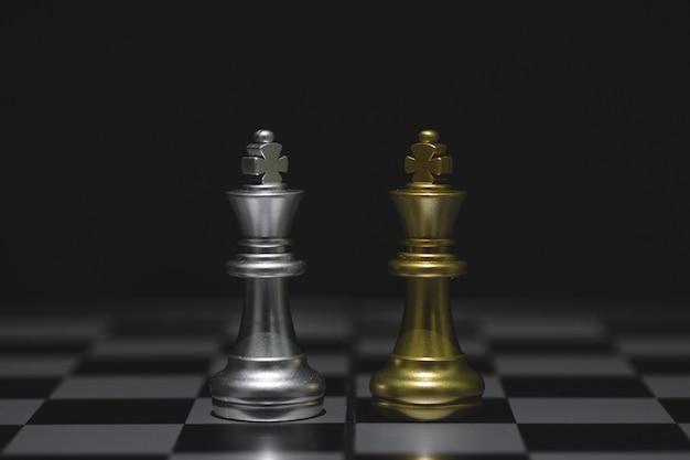 Die königschachfiguren kämpfen, goldenes und silbernes königschach auf einem schachbrett. geschäftsleiter-konzept