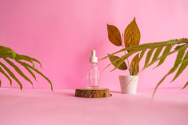 Die komposition enthält sommerprodukte. kosmetikflasche auf rundem holz auf rosafarbenem hintergrund mit getrockneten blättern dekoration.