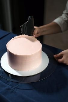 Die konditorin macht mit ihren eigenen händen eine hochzeitstorte und drückt die sahne auf die kuchenschichten.
