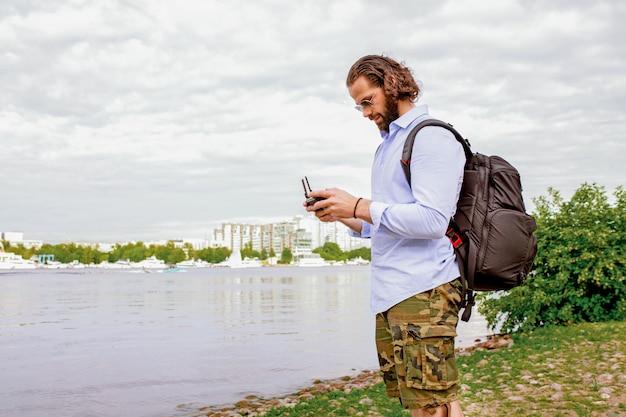Die konsole der drohne befindet sich in den händen eines jungen mannes. ein gutaussehender mann steuert einen quadrocopter.