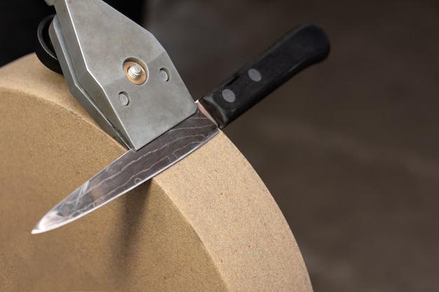 Die korrekte position des messerhalters und des messers selbst auf dem schleifstein.