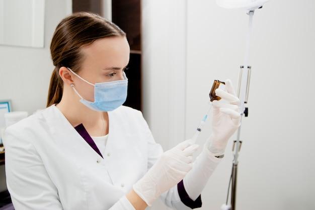 Die kosmetikerin bereitet sich darauf vor, injektionen in das gesicht des mannes zu machen, um narben und falten zu entfernen und es glatt und jung zu machen.