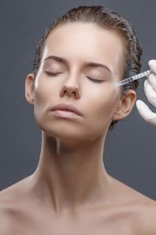 Die kosmetikerin des arztes führt das verjüngende verfahren für gesichtsspritzen durch, um falten auf der gesichtshaut einer frau in einer hautpflege für schönheitssalons in der kosmetik zu straffen und zu glätten
