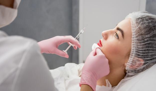 Die kosmetikerin des arztes führt die gesichtsinjektion durch. junge frau in einem schönheitssalon.