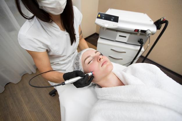 Die kosmetikerin des therapeuten führt eine laserbehandlung des gesichts einer jungen frau in der beauty spa-klinik durch.