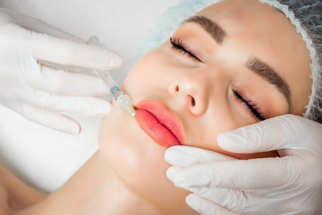 Die kosmetikerin führt das verfahren der verjüngenden gesichtsinjektion durch, um die falten auf der gesichtshaut einer schönen jungen frau in einem schönheitssalon zu straffen und zu glätten