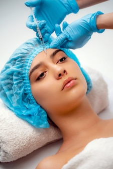 Die kosmetikerin führt das verfahren der verjüngenden gesichtsspritzen durch, um die falten auf der gesichtshaut einer frau in einem schönheitssalon zu straffen und zu glätten. kosmetik hautpflege