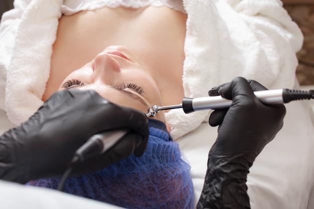 Die kosmetikerin führt den mikrostromvorgang durch