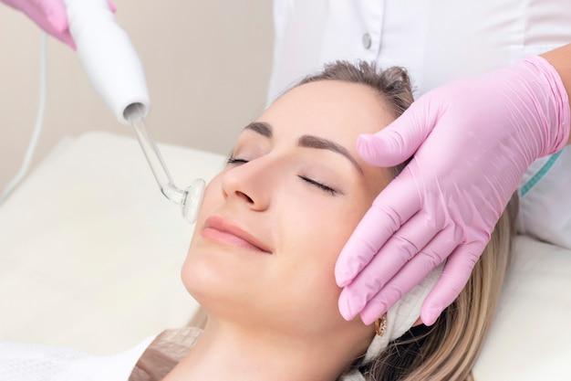 Die kosmetikerin führt ein pulsstromverfahren für das gesicht einer jungen frau durch.
