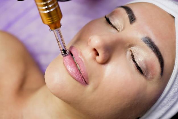 Die kosmetikerin injiziert dem patienten eine mesotherapie.