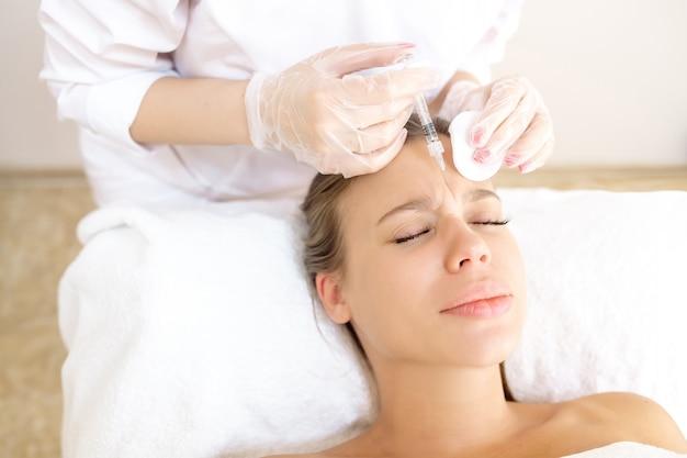Die kosmetikerin korrigiert den patienten mit botox in der stirn