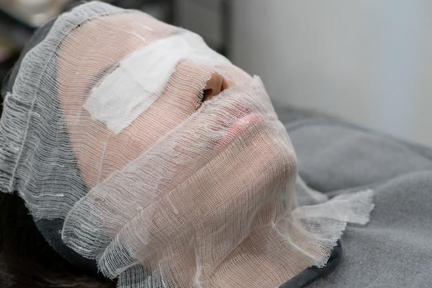 Die kosmetikerin legt einen verband ins gesicht. vorbereiten der gesichtshaut vor dem auftragen einer verjüngenden maske in einem schönheitssalon.