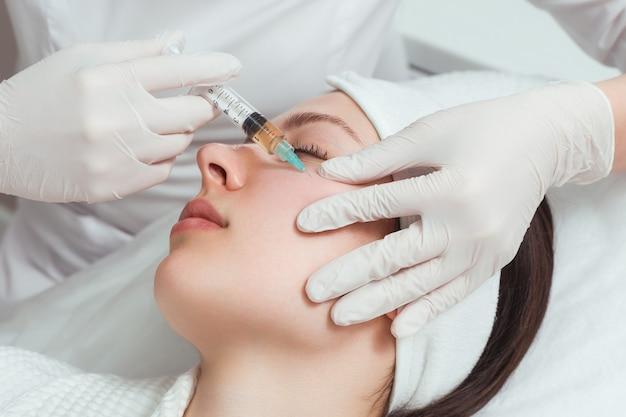 Die kosmetikerin macht anti-aging-injektionen für das gesicht, um falten auf dem gesicht zu straffen und zu glätten