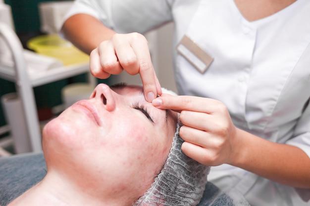 Die kosmetikerin macht eine gesichtskosmetikmassage und massiert den augenbrauenbereich