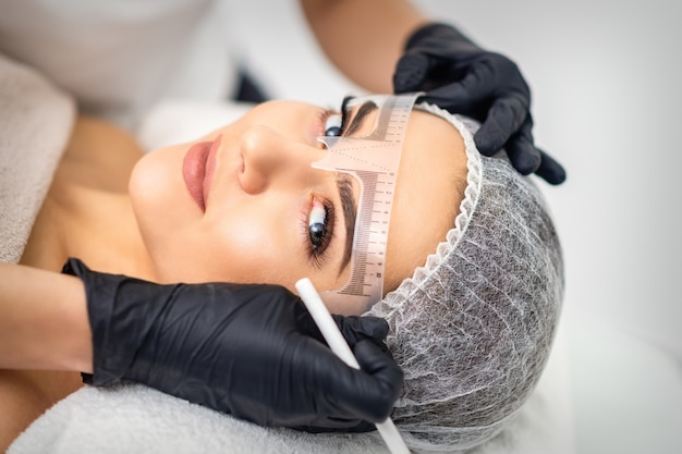 Die kosmetikerin misst mit dem lineal die brauen der jungen frau