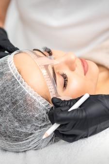 Die kosmetikerin misst mit dem lineal die brauen der jungen kaukasischen frau vor dem dauerhaften make-up-tattoo