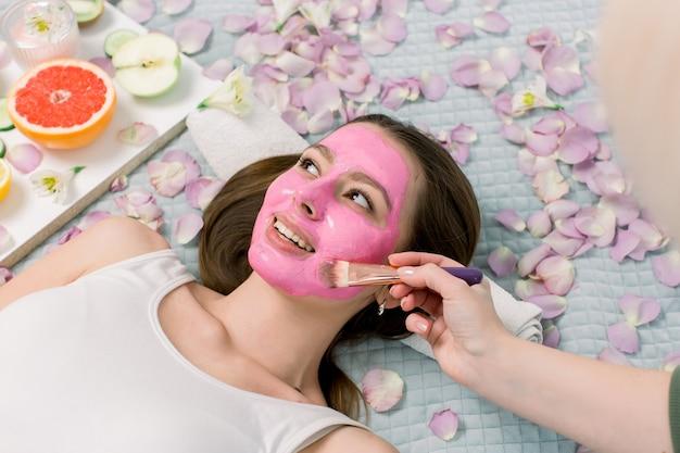 Die kosmetikerin schmiert der hübschen jungen frau im spa-salon eine kosmetische gesichtsmaske ins gesicht. gesichtsmaske, spa-schönheitsbehandlung, hautpflege.