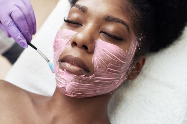 Die kosmetikerin trägt eine feuchtigkeitsmaske auf das gesicht des kunden auf