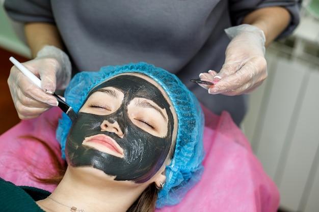 Die kosmetikerin trägt eine schwarze maske auf, um das gesicht eines jungen mädchens mit einem pinsel zu schälen. eine kosmetikerin führt ein peeling an einem jungen mädchen durch, das auf einer couch liegt.