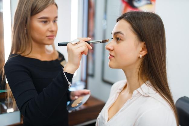 Die kosmetikerin trägt make-up auf das gesicht einer frau im kosmetikgeschäft auf. luxus-schönheitssalon, kundin und kosmetikerin im modemarkt