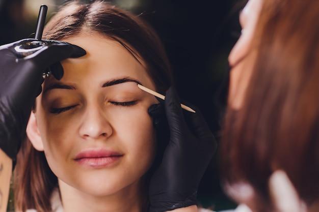 Die kosmetikerin und maskenbildnerin trägt in der sitzungskorrektur in einem schönheitssalon henna auf zuvor gezupfte, gestaltete, gestrichene augenbrauen auf. professionelle gesichtspflege.