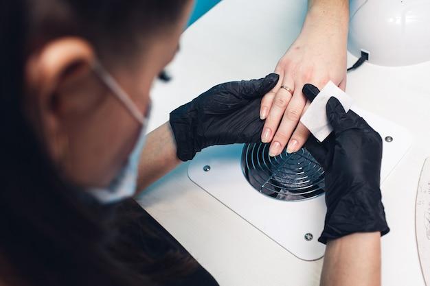 Die kosmetikerin untersucht und wischt die nägel des kunden mit einer serviette ab. vorbereitung für eine maniküre.