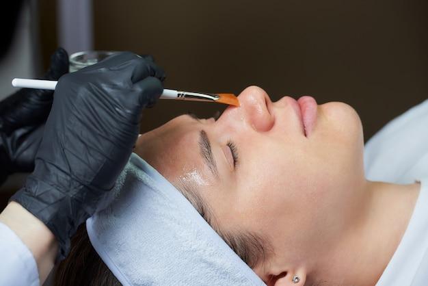 Die kosmetikerin verwendet einen pinsel, um der frau ein oberflächliches gesichtspeeling aufzutragen.