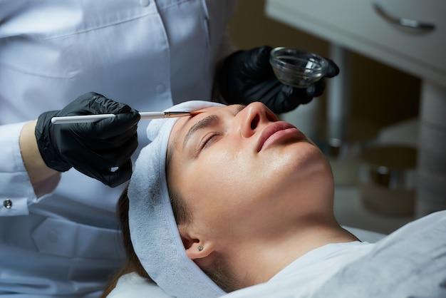 Die kosmetikerin verwendet einen pinsel, um ein transparentes gesichtspeeling auf die frau aufzutragen.