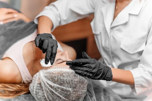 Die kosmetikerin wischt die augenbrauenfarbe mit einem wattestäbchen ab. permanentes brauenmake-up im schönheitssalon, abschluss oben. kosmetologische behandlung.