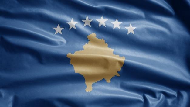Die kosovarische flagge weht im wind. nahaufnahme von kosovo-banner weht, weiche und glatte seide. stoff textur fähnrich hintergrund. verwenden sie es für das konzept für nationalfeiertage und länderanlässe.