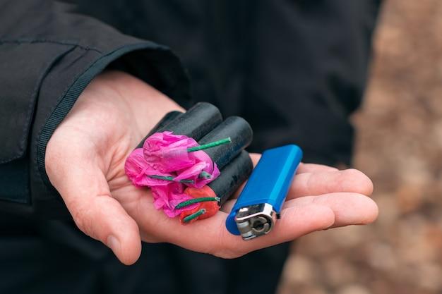 Die kracher in der hand. mann, der fünf schwarze petarden mit einem blauen gasfeuerzeug auf seiner handfläche hält.