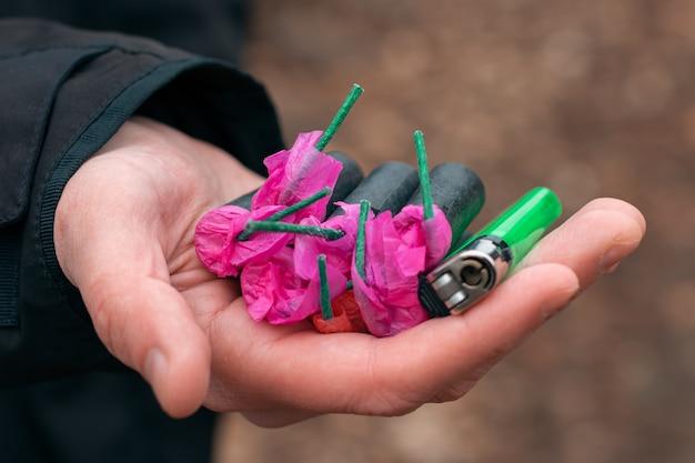 Die kracher in der hand. mann, der fünf schwarze petarden mit einem grünen gasfeuerzeug auf seiner handfläche hält.