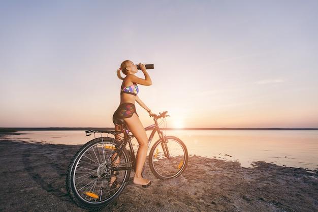 Die kräftige blonde frau im bunten anzug sitzt auf dem fahrrad, trinkt wasser aus einer schwarzen flasche in einer wüstengegend am wasser. fitness-konzept.