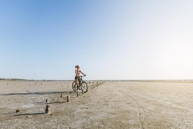 Die kräftige blonde frau in buntem anzug und sonnenbrille sitzt auf einem fahrrad in einer wüstengegend und schaut in die sonne. fitness-konzept.