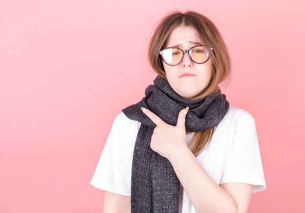 Die kranke junge frau zeigt mit dem finger auf den raum rechts von ihr. porträt eines kranken mädchens mit einem schal um den hals auf einem rosa hintergrund.