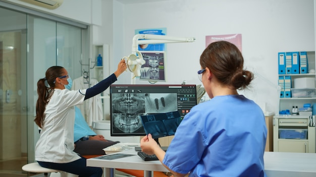 Die krankenschwester des stomatologen vergleicht röntgenaufnahmen mit blick auf den computer, während der facharzt mit gesichtsmaske mit einem mann mit zahnschmerzen spricht, der auf einem stomatologischen stuhl sitzt und werkzeuge für die operation vorbereitet