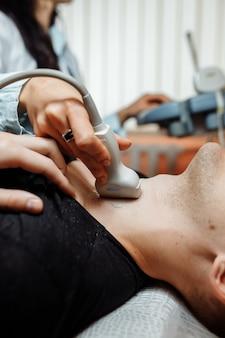 Die krankenschwester führt im büro einen ultraschall am hals des patienten durch
