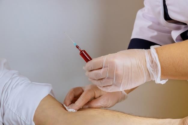 Die krankenschwester für medizinhandschuhe nimmt das blut in das reagenzglas, eine menschliche blutprobe für covid-19