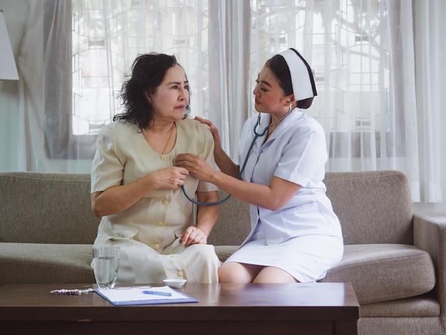 Die krankenschwester kümmert sich glücklich um ältere menschen, alte frauen empfinden herzschmerzen