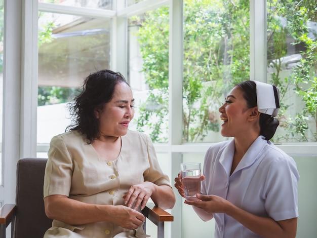 Die krankenschwester kümmert sich glücklich um ältere menschen