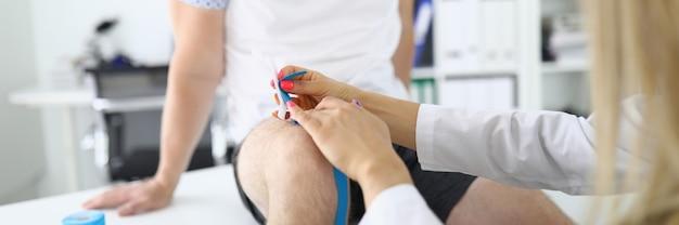 Die krankenschwester repariert das kinesio-klebeband am knie des mannes