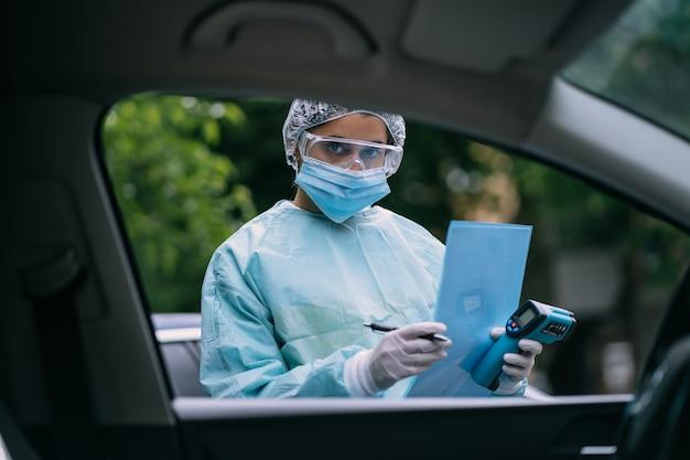 Die krankenschwester trägt während des covid19-ausbruchs einen schutzanzug und eine maske.