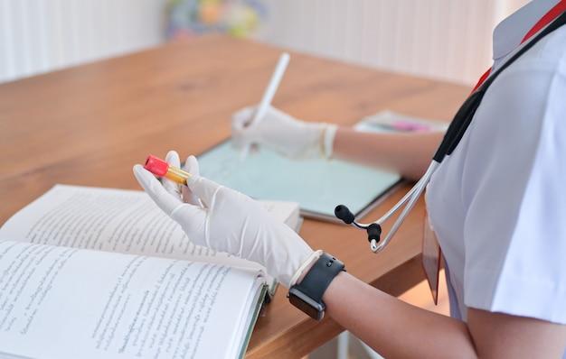 Die krankenschwester zeichnet patientendaten auf und vergleicht die ergebnisse von blutreagenzgläsern mit tabletten